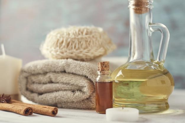 Serviettes, bougie et huile de massage sur table blanche Photo Premium