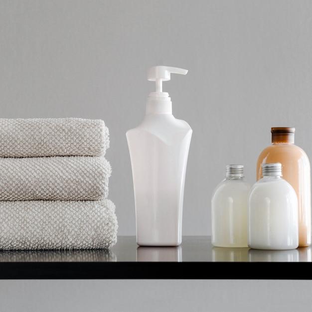 Serviettes, bouteilles avec shampoing, revitalisant, lait de douche et savon artisanal. Photo Premium
