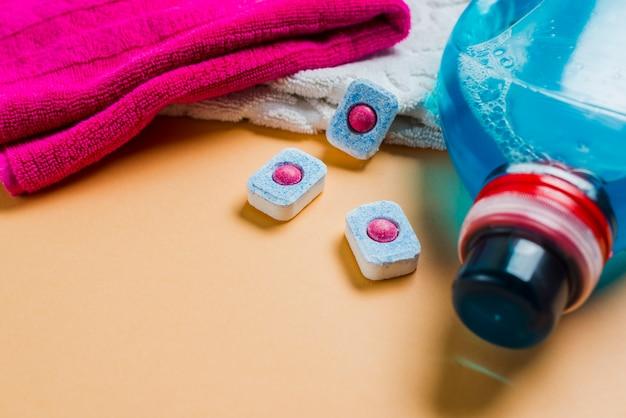Serviettes colorées et détergent liquide avec tablettes pour lave-vaisselle Photo gratuit