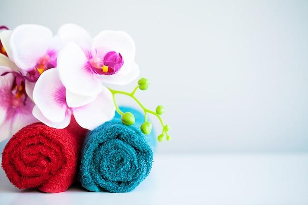 Serviettes colorées et orchidées sur une table blanche avec espace de copie sur fond de salle de bain. Photo Premium