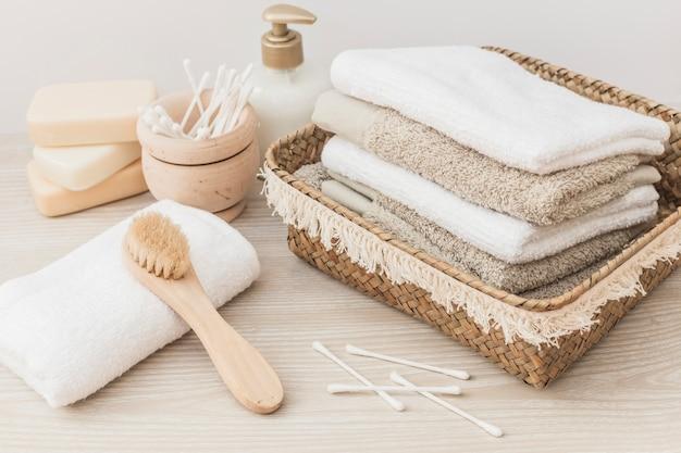 Serviettes empilées; brosse; savon; coton-tige et bouteille cosmétique sur fond en bois Photo gratuit