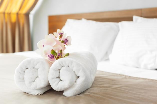Serviettes et fleurs sur le lit dans la chambre d'hôtel Photo Premium
