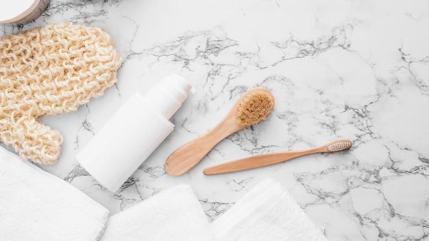 Les serviettes; gant de gant; pinceau et bouteille cosmétique sur fond de marbre Photo gratuit