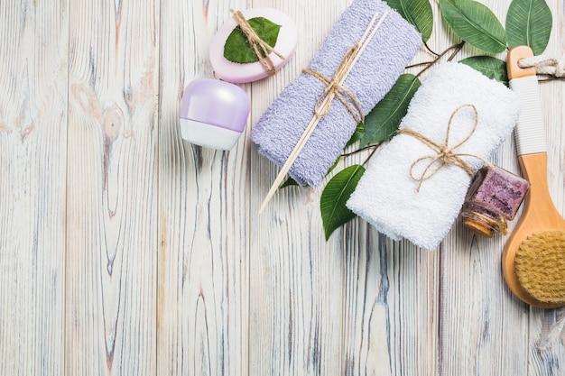 Les serviettes; récurer la bouteille; crème hydratante; feuilles; brosse et savon sur planche de bois Photo gratuit