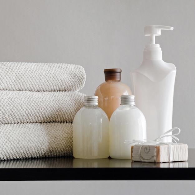 Serviettes avec shampoing, revitalisant, lait de douche et savon artisanal sur fond neutre. concept spa Photo Premium