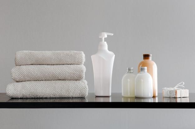 Serviettes avec shampoing, revitalisant, lait de douche et savon artisanal Photo Premium