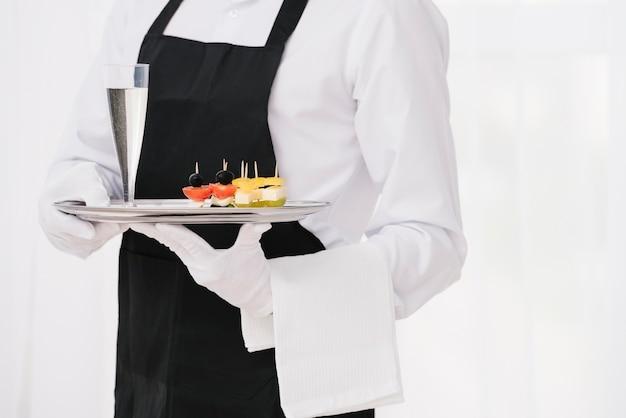 Serviteur en uniforme tenant un plateau Photo gratuit