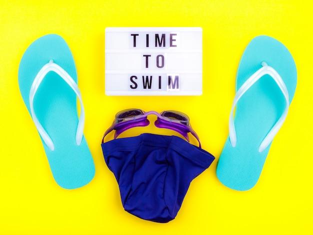 Set de natation - pantoufles, serviette, lunettes de protection, bonnet de bain Photo Premium
