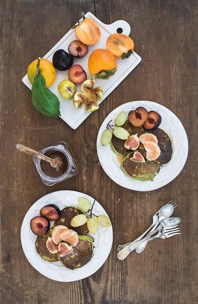 Set de petit déjeuner. galettes de courgettes faites maison avec prune fraîche, mandarine, raisins, figues et miel dans des assiettes en céramique blanches sur du bois rustique. Photo Premium