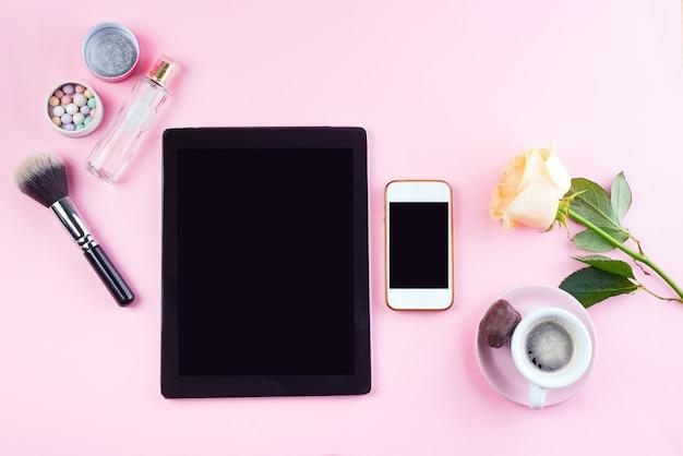 Set plat de tablette et téléphone avec une tasse de café, verres, rose et parfum sur rose, maquette Photo Premium
