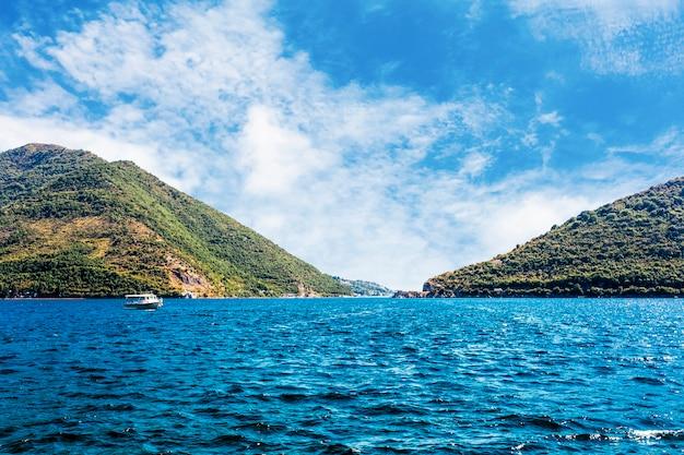 Seul bateau sur le lac calme bleu près de la montagne verte Photo gratuit