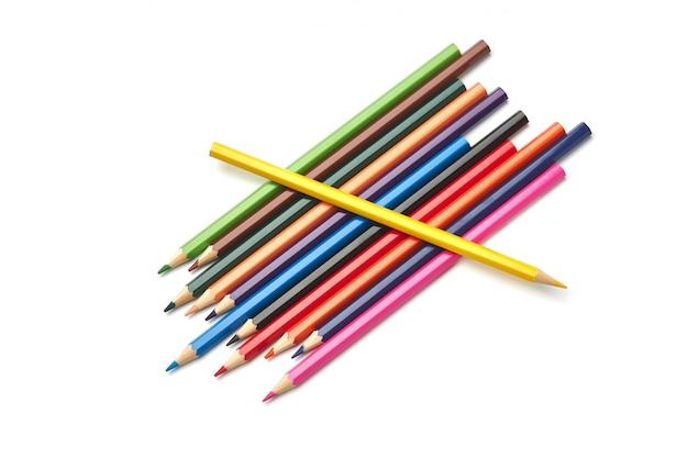 Seul un crayon jaune repose sur une pile d'autres crayons de couleur Photo Premium