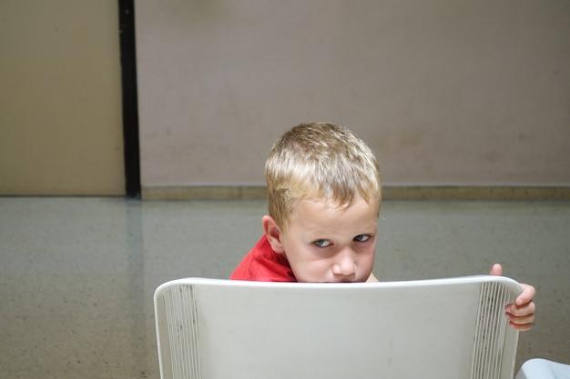 Seul enfant et orphelin attend effrayé dans le fauteuil d'une salle d'attente. Photo Premium