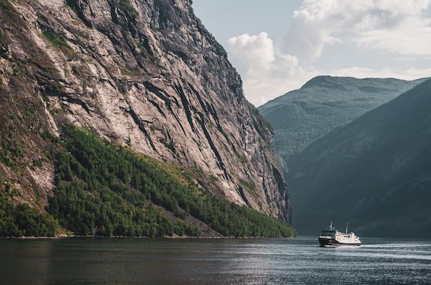 Seul Navire Dans Le Lac Entouré De Hautes Montagnes Rocheuses Sous Le Ciel Nuageux En Norvège Photo gratuit