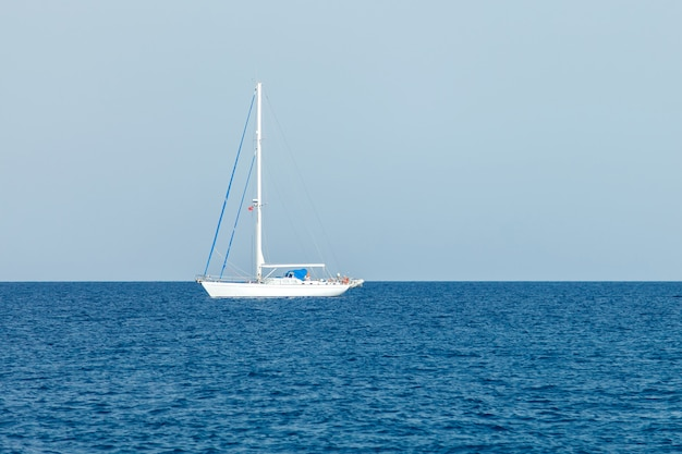 Un seul yacht blanc à voiles basses se dresse dans les eaux de la mer méditerranée Photo Premium