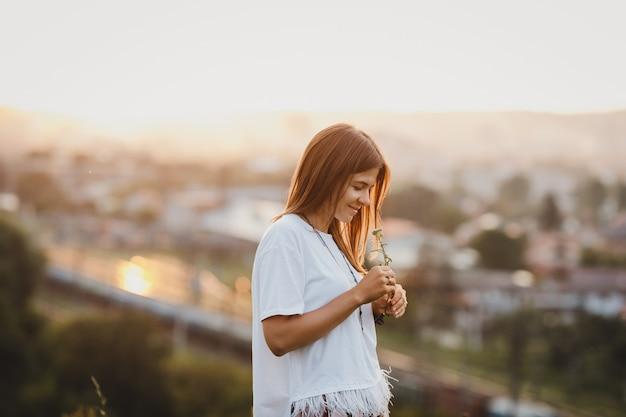 Seule femme en chemise blanche se dresse avec une fleur de champ Photo gratuit