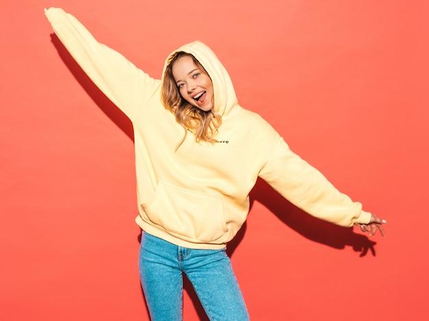 Sexy Femme Insouciante Posant Près Du Mur Rose. Modèle Positif S'amusant, Levant Les Mains Photo gratuit