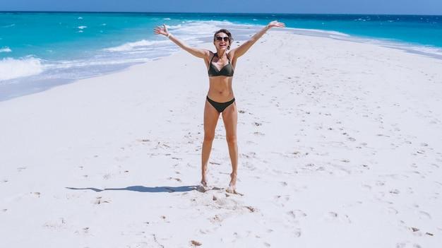 Sexy femme en maillot de bain debout sur le sable de l'océan Photo gratuit