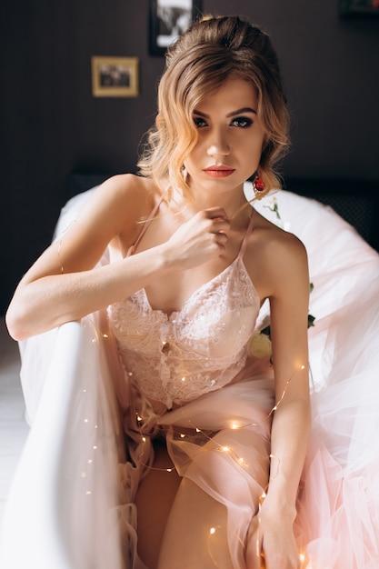 Sexy jeune blonde en lingerie pétillante se trouve dans la salle de bain recouverte de soie Photo gratuit