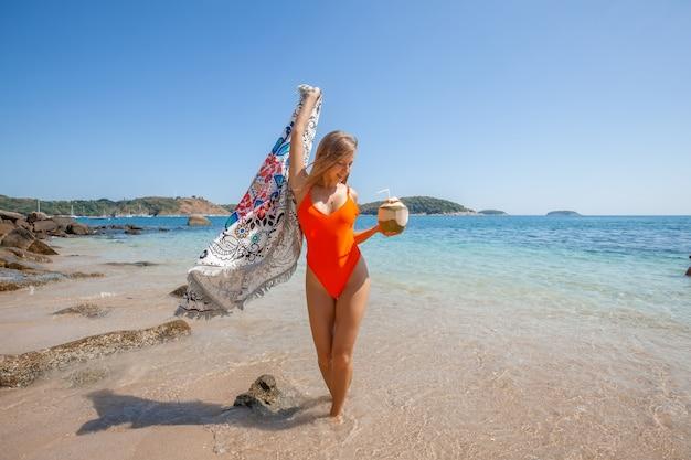 Sexy jeune fille s'amuser sur la plage avec de la noix de coco fraîche et un chiffon de plage Photo Premium