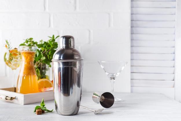 Shaker à cocktail, swizzle, pinces et cuillère à glace dans un seau pour préparer un cocktail d'été Photo Premium