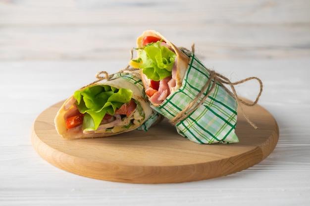 Shaurma enveloppé sandwich avec jambon tomates laitue et fromage sur une plaque de bois Photo Premium