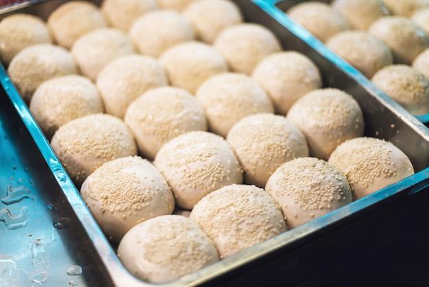 Sheng jian bao, petit pain de porc blanc nappé de sésame avant la friture. Photo Premium
