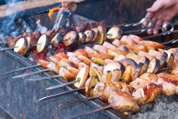 Shish kebab avec des pommes de terre à rôtir sur le gril. bbq party. Photo Premium