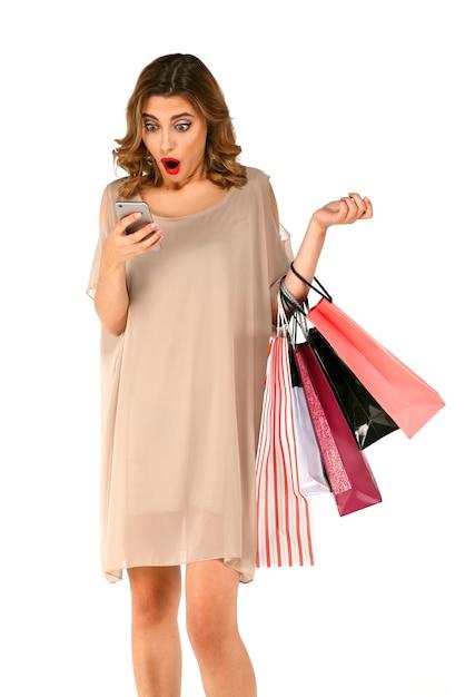 Shopper choqué femme avec des sacs à provisions a vu une grande réduction dans l'application sur le téléphone intelligent. Photo gratuit