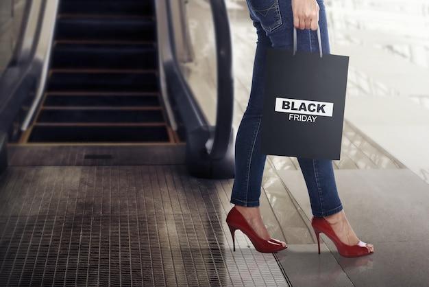 Shopper femme avec sac en papier black friday Photo Premium
