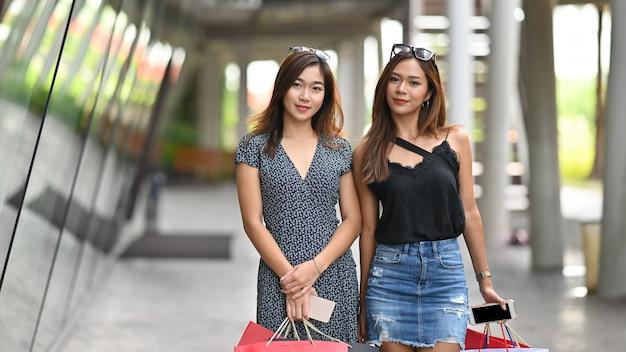 Shopping asiatique avec portrait tourné avec un sac à provisions sur les mains. Photo Premium
