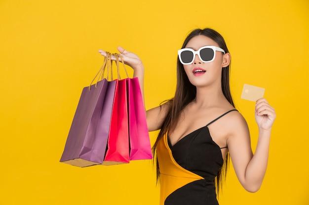 Shopping belle femme portant des lunettes avec une carte de crédit en or avec un sac en papier coloré sur un jaune. Photo gratuit