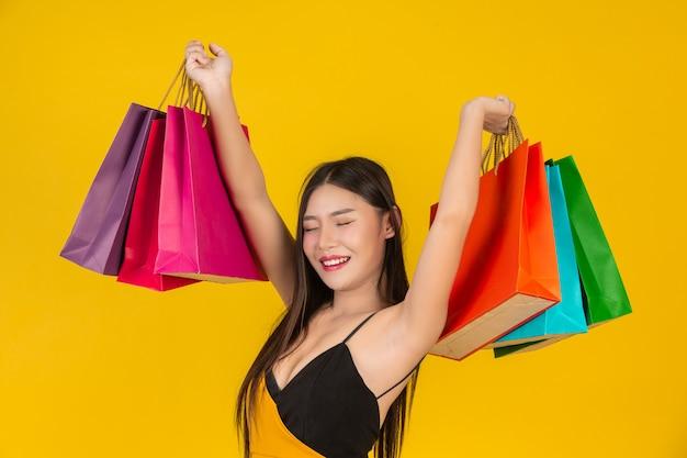 Shopping Belle Femme Tenant Un Sac En Papier Coloré Sur Un Jaune. Photo gratuit
