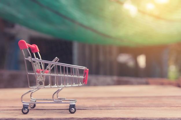 Shopping concept - caddie vide rouge sur une table en bois marron. les consommateurs en ligne peuvent faire leurs achats à domicile et en livraison. Photo Premium