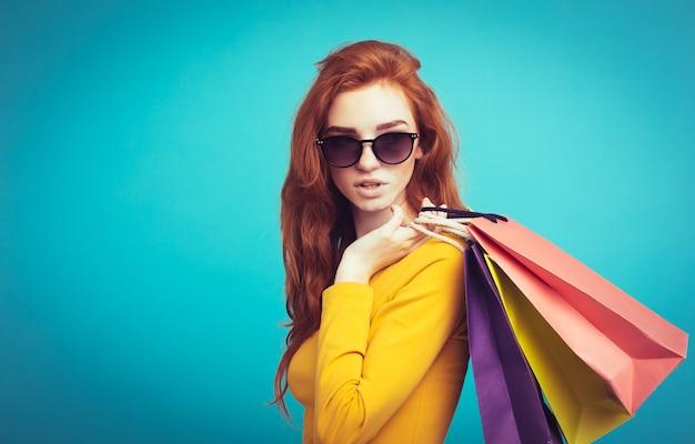 Shopping concept - close up portrait jeune belle fille sexy redhair souriante regardant la caméra avec un sac à provisions. blue pastel background. espace de copie. Photo gratuit