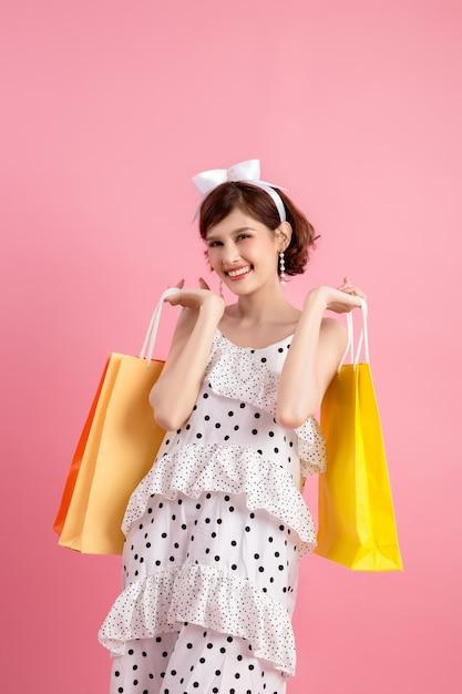 Shopping femme tenant des sacs à provisions rose Photo gratuit