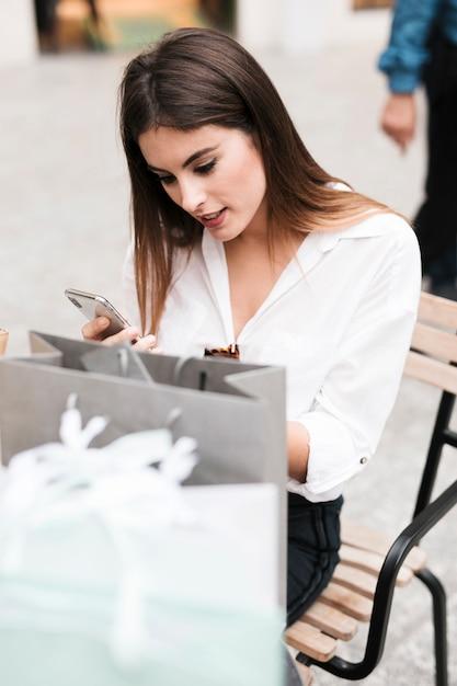 Shopping fille en regardant son téléphone portable Photo gratuit