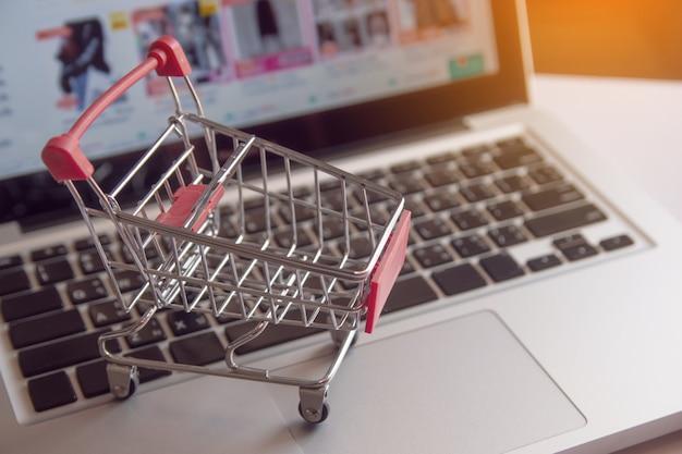 Shopping en ligne concept - panier ou chariot sur un clavier d'ordinateur portable. service d'achat sur le web en ligne. avec espace de copie Photo Premium