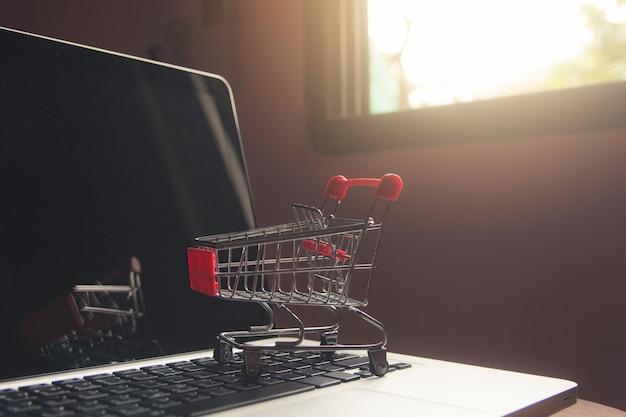 Shopping en ligne concept - panier ou chariot sur un clavier d'ordinateur portable. service d'achat sur le web en ligne. Photo Premium