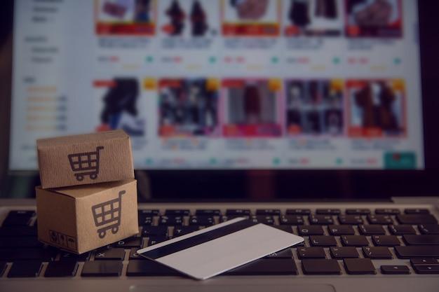 Shopping en ligne concept - service d'achat sur le web en ligne. avec paiement par carte de crédit et offre la livraison à domicile. colis ou des cartons en papier avec le logo d'un panier d'achat sur un clavier d'ordinateur portable Photo Premium