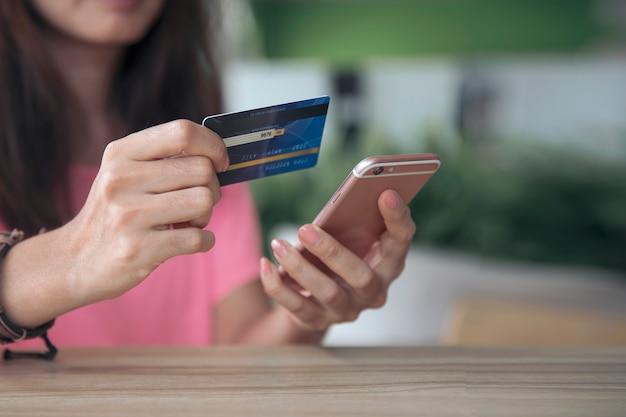 Shopping, paiement en ligne avec carte de crédit, femme utilisant un smartphone mobile, entreprise e-commerce et concept d'application Photo Premium