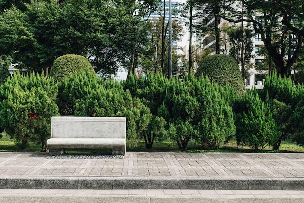 Siège de pierre dans un parc avec des pins en arrière-plan. Photo Premium