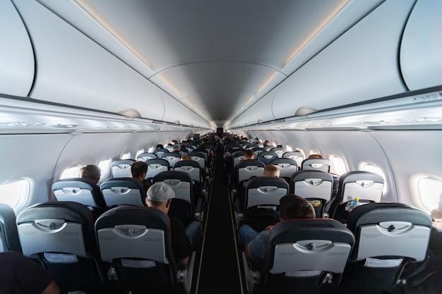 Sièges cabine avec passagers. classe économique des nouvelles compagnies aériennes les moins chères et les moins chères sans retard ni annulation de vol. voyage dans un autre pays. Photo Premium