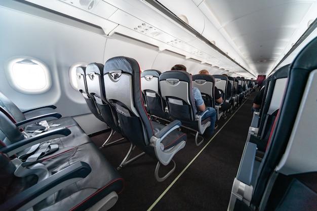 Sièges cabine avec passagers. classe économique des nouvelles compagnies aériennes les moins chères et les moins chères. voyage dans un autre pays. turbulence en vol. Photo Premium