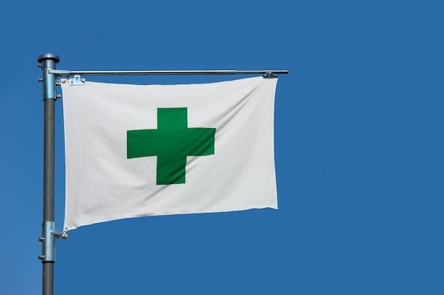 Un signe de croix verte, drapeau de secourisme de sécurité sur fond de ciel bleu. Photo Premium