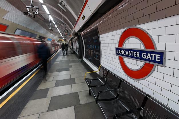 Signe du métro de londres avec le train en mouvement et les gens à la gare de lancaster gate Photo Premium