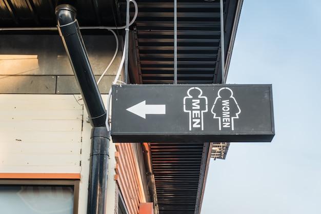 Signe de toilette par bombe de peinture blanche sur le bâtiment Photo Premium