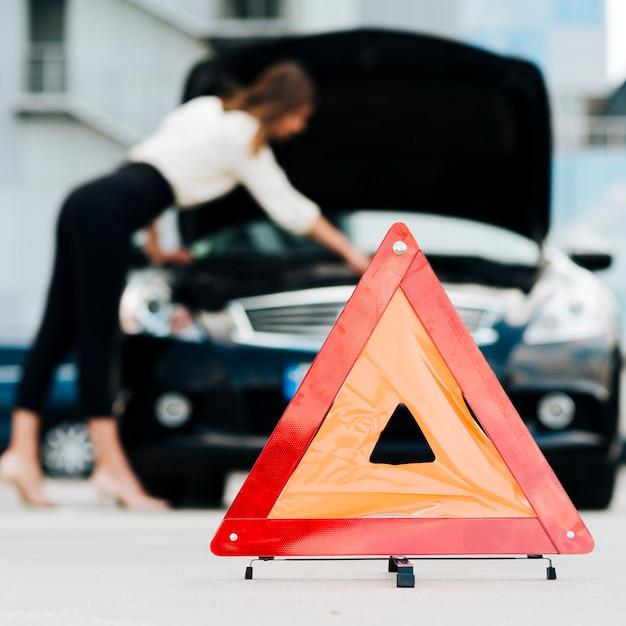 Signe d'urgence avec voiture en arrière-plan Photo gratuit