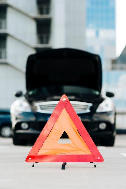 Signe d'urgence avec voiture noire en arrière-plan Photo gratuit