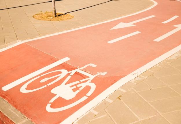Signe de vélo blanc avec flèche dans la rue Photo gratuit